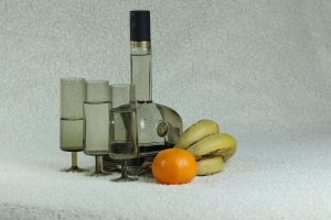 Still life with a bottle and glasses and fruits
